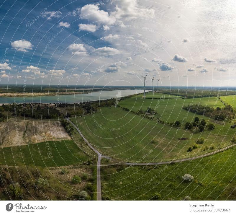 Alternative Energie - Räder eines Windgenerators im Lufthintergrund mit Feldern und einem See. Rad Natur Umwelt gewinnt alternativ grün Chance Himmel Antenne