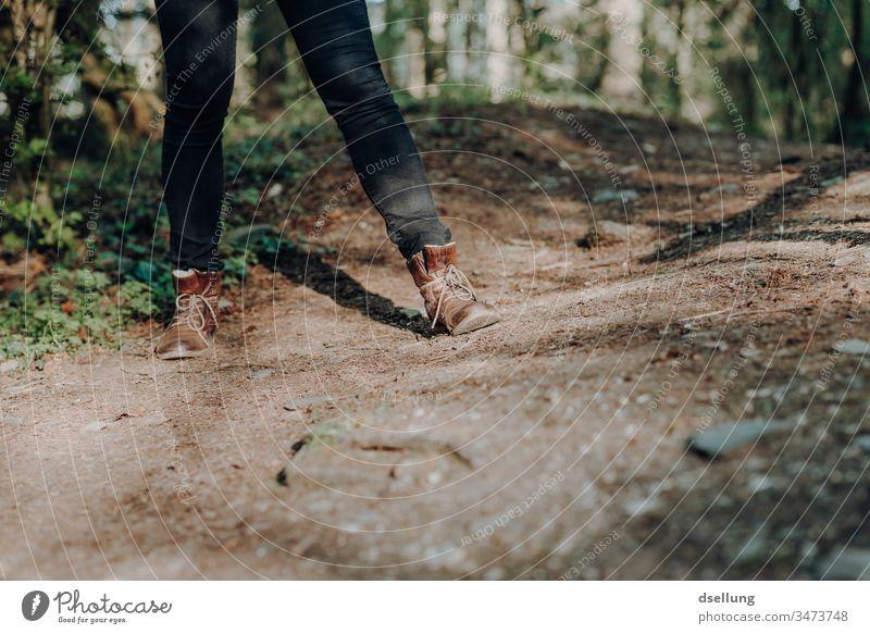 Beine einer jungen Frau mit schwarzer Jeans und braunen Lederstiefeln auf einem Waldweg Wege & Pfade Schuhe Lifestyle wandern Frauenbein