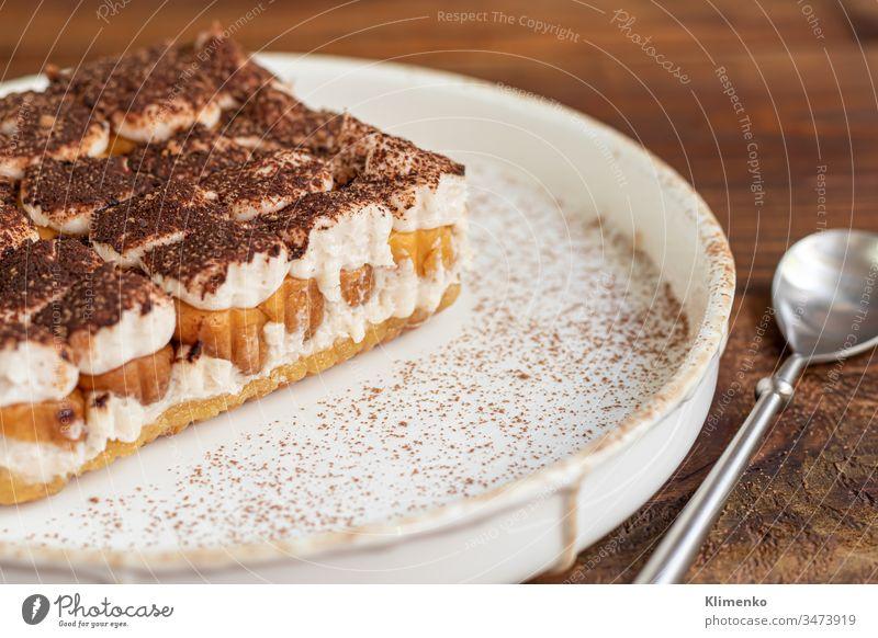Tiramisu. Traditionelles italienisches Dessert auf Holzuntergrund. Garniert mit einem Zweig Minze, Limettenscheiben. In einer transparenten Tasse Tee mit Sanddorn.