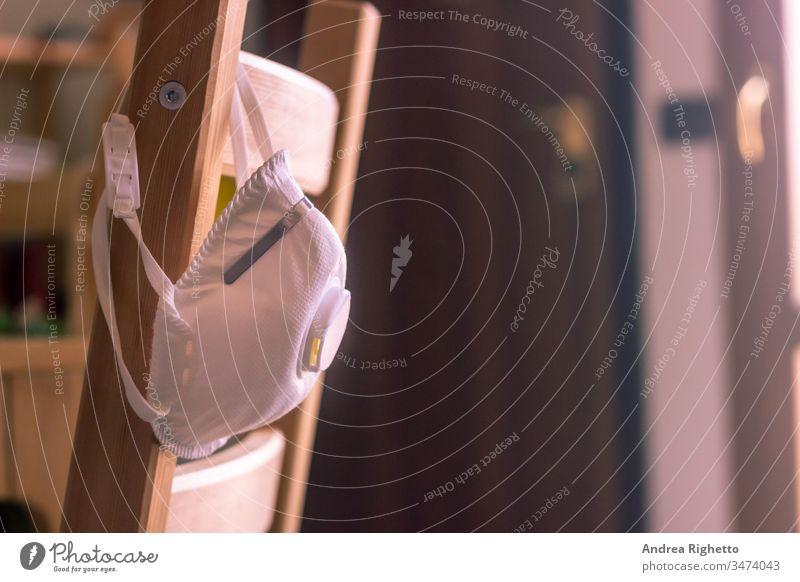 Weiße Maske auf einem Stuhl. Die Maske schützt vor dem Pandemievirus SARS-CoV-2 oder Coronavirus oder COVID-19, das sich in der Luft verbreitet. Trauriger Ton