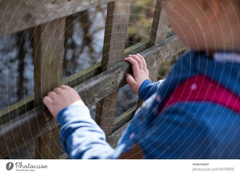 Kind hält sich an Geländer fest Corona draußen kind mädchen spielen draussen geländer kita absperrung zooz zaun natur wald spaziergang entdecken hand