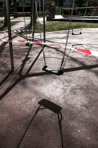 Spielplatz, Schaukel, Absperrband gegenlicht schatten schaukel spielplatz aussenaufnahme gesperrt abgesperrt verboten coronakrise isolation menschenleer