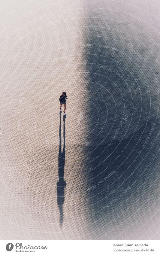 Frau läuft auf der Straße in der Stadt Bilbao Spanien Person rennen Läufer Sport Straßenfotografie im Freien Schatten Silhouette Großstadt Übung trainiert.