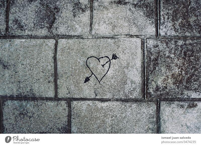 Herz an der grauen Wand auf der Straße, Liebe liegt in der Luft Pfeil Farbe Malerei zeichnen Zeichnung texturiert Hintergrund Gemälde Kreativität streichen