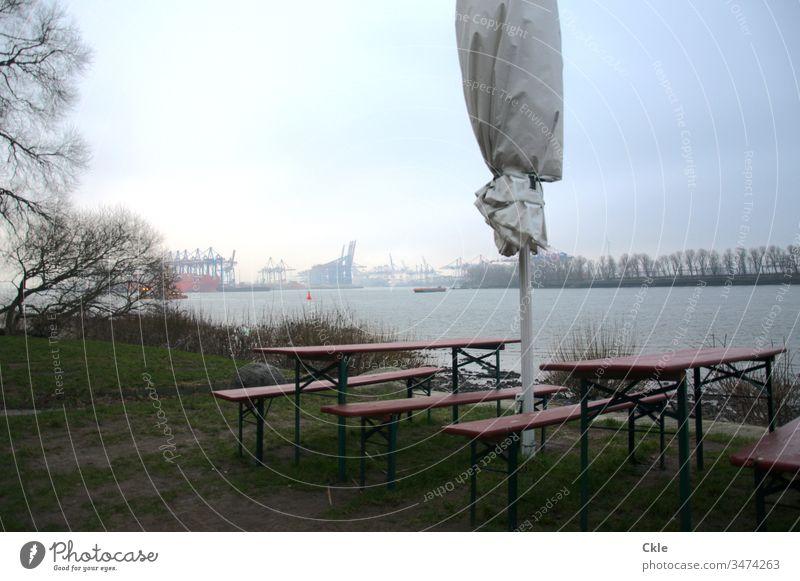 Bänke und Stühle am Elbufer, Blick auf Hafenanlagen Elbe Hamburg Gastronomie Sonnenschirm Fluss Gras Ufer Hamburger Hafen Kräne Lockdown Weite Wasser Strom