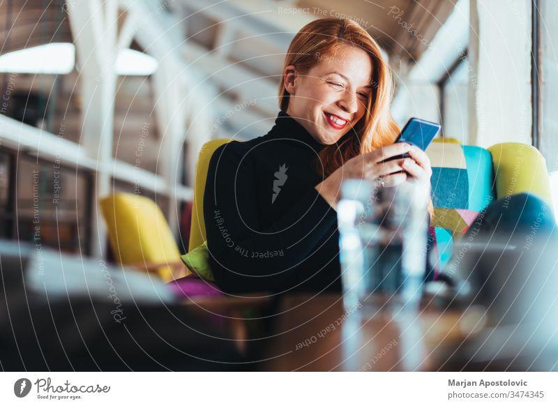 Junge glückliche Frau benutzt Smartphone in einem Cafe jung Glück Lächeln Café im Innenbereich lässig Tisch Sitzen Lifestyle verbunden Anschluss Mobile Telefon