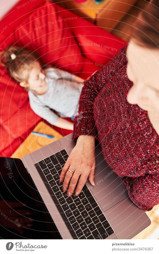 Mutter einer Frau, die während der COVID-19-Quarantäne von zu Hause aus per Video-Chat-Call-Stream-Online-Kurs Webinar auf einem Laptop durchführt, während ihre Tochter sich ein Video auf einem Tablet anschaut. Frau sitzt im Bett vor dem Computer und schaut auf den Bildschirm