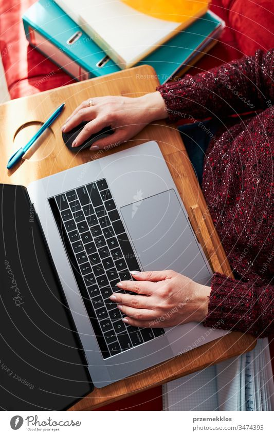 Mutter einer Frau, die während der COVID-19-Quarantäne während eines Video-Chat-Call-Stream-Online-Kurses auf einem Laptop von zu Hause aus ihren Job aus der Ferne erledigt. Frau sitzt im Bett vor dem Computer und schaut auf den Bildschirm