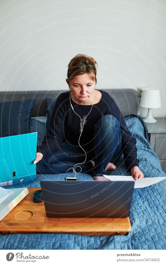 Frau, die während eines Video-Chat-Call-Stream-Online-Kurses per Webinar auf einem Laptop von zu Hause aus ihren Job aus der Ferne erledigt. Frau sitzt im Bett vor dem Computer und schaut mit Kopfhörern und Smartphone auf den Bildschirm
