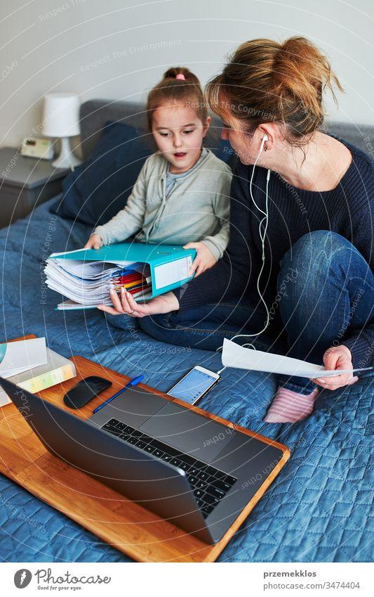 Die Mutter einer Frau, die während eines Video-Chat-Call-Stream-Online-Kurses auf einem Laptop von zu Hause aus ihren Job aus der Ferne erledigt, während ihre Tochter während der COVID-19-Quarantäne herumspielt. Frau sitzt im Bett vor dem Computer, schaut auf den Bildschirm und benutzt Kopfhörer