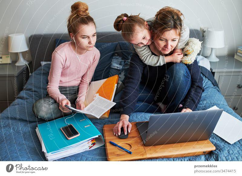 Mutter und Tochter von Frauen, die während der COVID-19-Quarantäne aus der Ferne lernen, indem sie während der Video-Chat-Call-Stream-Online-Kurs Webinar-Lektionen auf einem Laptop von zu Hause aus erledigen. Frauen sitzen im Bett vor dem Computer und schauen auf den Bildschirm