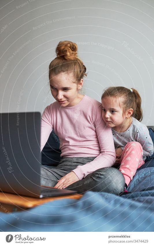 Teenagermädchen und ihre jüngere Schwester spielen beim Lernen am Laptop und verbringen während der COVID-19-Quarantäne Zeit miteinander zu Hause. Mädchen sitzen im Bett vor dem Computer
