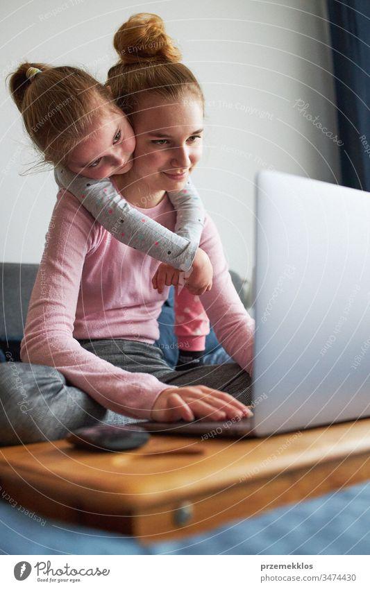 Enkelkinder, Teenagermädchen und ihre jüngere Schwester unterhalten sich während der COVID-19-Quarantäne per Videoanruf mit den Großeltern per Laptop von zu Hause aus. Mädchen sitzen im Bett vor dem Computer