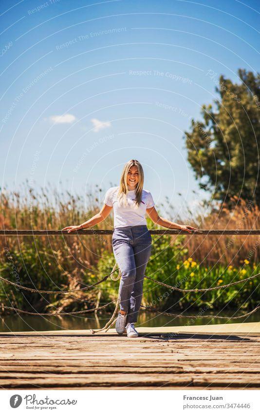 Junge elegante glückliche Frau posiert auf einem Pier Erwachsener Teenager blond kolumbianisch Spanien Mädchen jung attraktiv Tag stylisch im Freien Lächeln