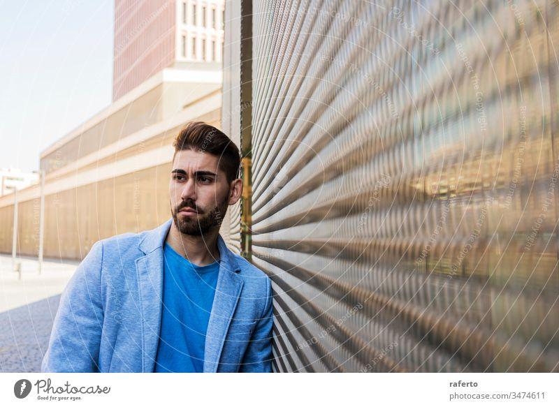 Junger bärtiger Mann, Modell der Mode, im städtischen Hintergrund, in legerer Kleidung, während er an einer Wand lehnt und zur Seite schaut cool Stil Porträt