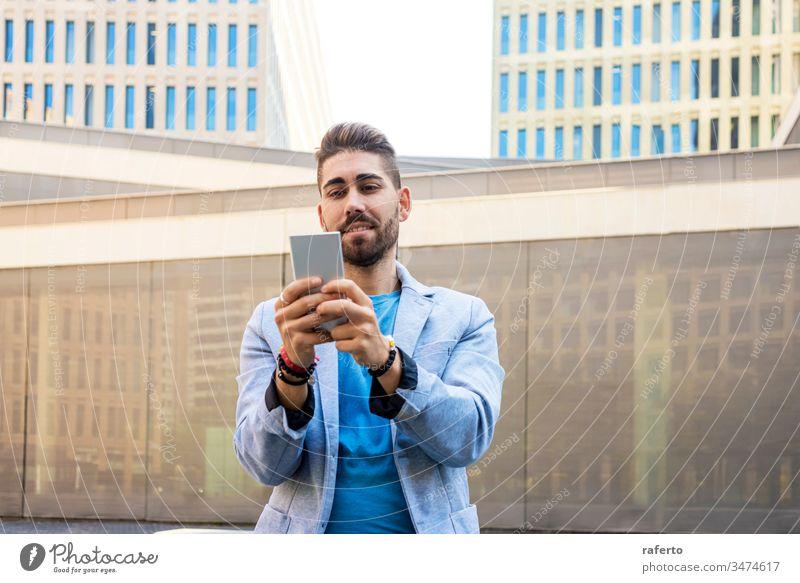 Porträt eines hübschen bärtigen jungen Mannes, der lächelt, wenn er sein Mobiltelefon benutzt Stil Typ Handy Sonnenbrille Hipster Lächeln 1 photogen Vollbart