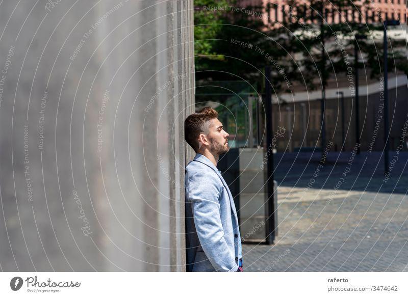 Nachdenklicher junger bärtiger Mann, der auf der Straße wegschaut, während er draußen an einer Wand lehnt Unsicherheit Geschäftsmann Denken Enttäuschung