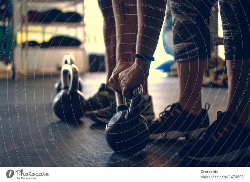 Detail eines Mannes, der eine auf dem Boden einer Turnhalle aufgestellte Kettlebell hält Athlet Fitnessstudio Gewichte Tatkraft trainiert. im Innenbereich