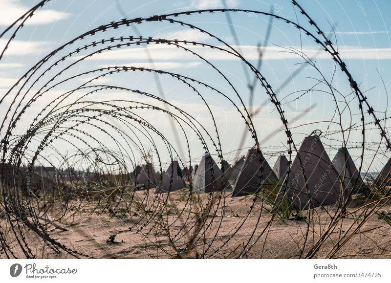 Stacheldraht und Beton-Militärzaun am Strand nahe dem Meer auf der Krim Russland Ukraine Annektierung Armee Verbot mit Stacheln versehen Barriere blau Borte