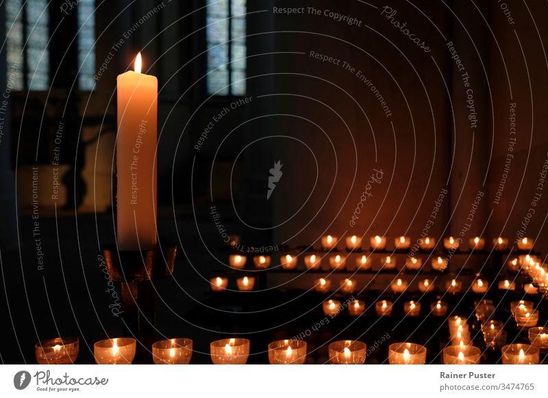 Eine große Kerze und viele kleine Kerzen in einer Kirche Kerzenschein innerhalb einer Kirche Religion Glaube religiös Religion & Glaube Christentum Hoffnung