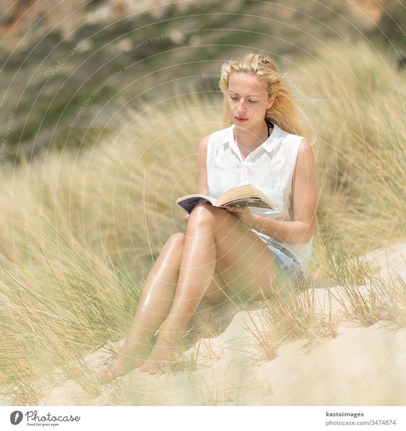 Eine Frau liest ein Buch und genießt die Sonne am Strand. Sommer lesen Natur frei Glück sorgenfrei sich[Akk] entspannen Wind Freude Freiheit Fröhlichkeit