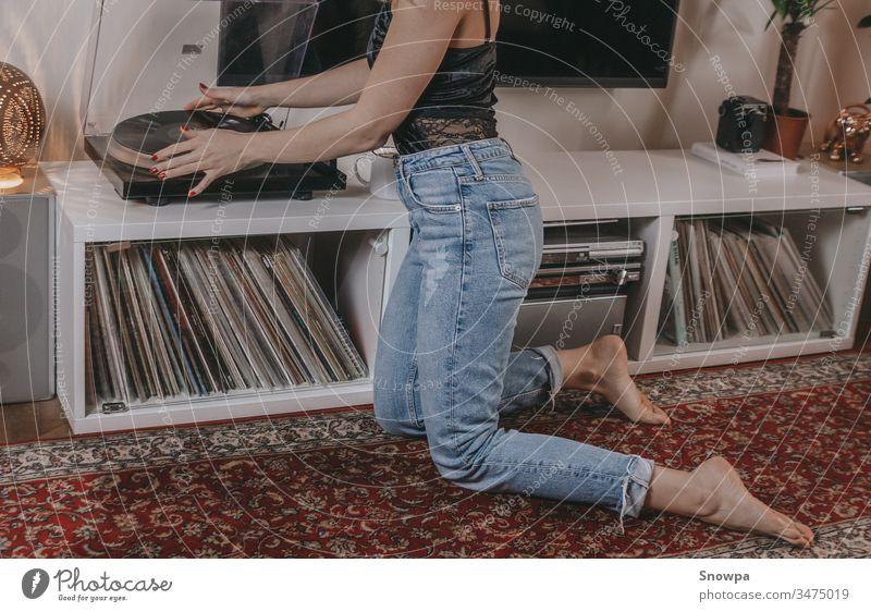 Junge Frau legt eine Schallplatte auf. Album analog Audio Barfuß schön Schönheit schwarze Spitze blond Bohemien Boho-Lebensstil lässig Kaukasier Entertainment