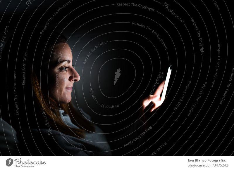 junge Frau zu Hause, die ein Mobiltelefon benutzt. Nachtzeit Handy heimwärts Bildschirm dunkel sich[Akk] entspannen Technik & Technologie Lifestyle Freizeit