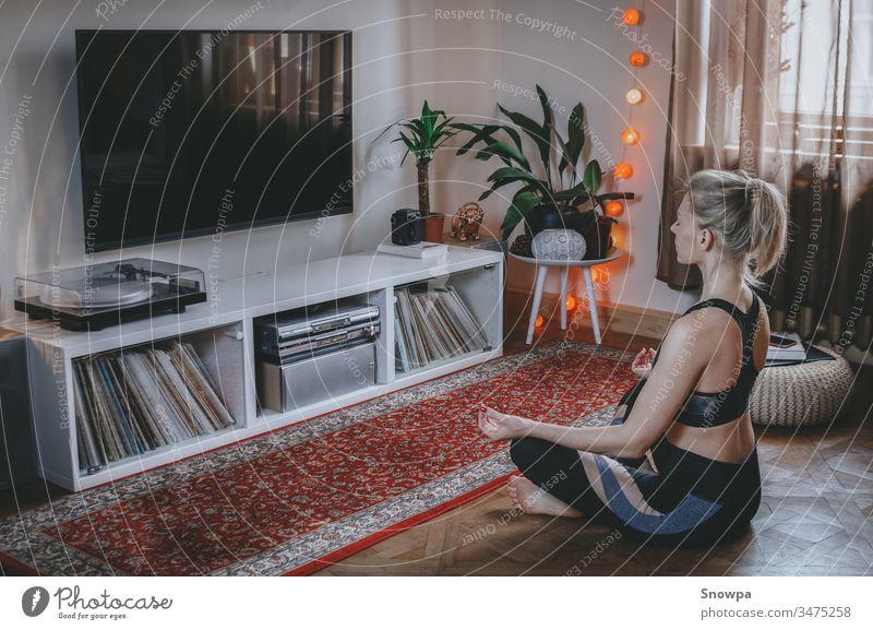 Junge Frau beim Meditieren im Wohnzimmer. Zu Hause gesund bleiben. attraktiv schön Schönheit Boho-Chic boho innen Windstille Pflege bequem Übung Fitness flach