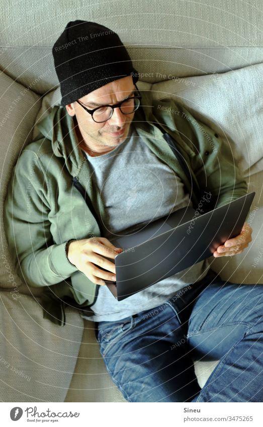 HomeOffice: entspannter Mann liegt auf dem Sofa mit seinem Notebook Homeoffice Arbeitsplatz Mütze Hipster Jeanshose Brille lässig leger selbständig freelancer