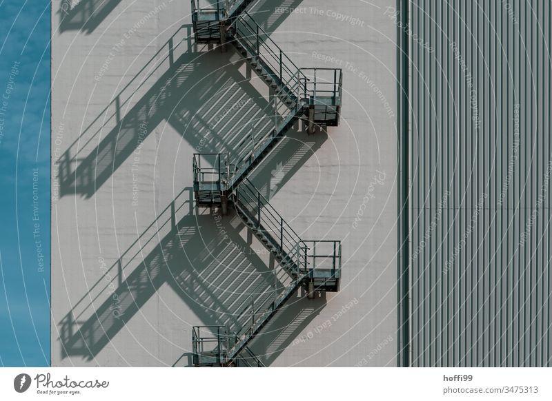 Fluchtweg an Gebäude mit eindrucksvollem Schattenwurf Notausgang Nottreppe Wendeltreppe Treppe Lagerhaus Lagerhalle Treppengeländer Hochhaus Fabrik Bauwerk
