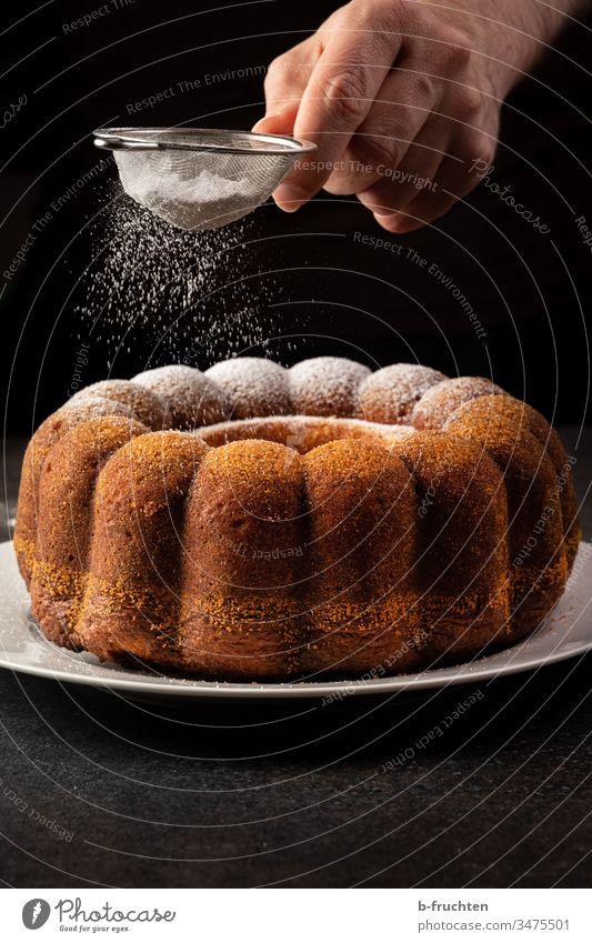 Kuchen mit Puderzucker bestreuen süß lecker Backwaren Süßigkeit Zucker staubzucker Hand Küche zubereiten zubereitung