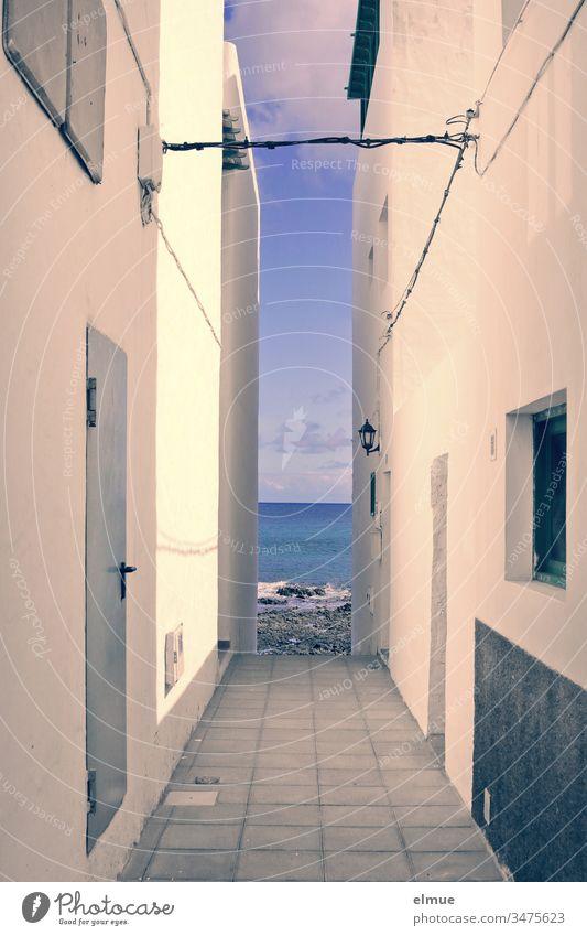 Blick aufs Meer zwischen zwei Häusern hindurch Meerblick Haus eng Durchblick Einschränkung Mauer Fassade Gasse Gebäude verbaut Menschenleer Architektur Wand