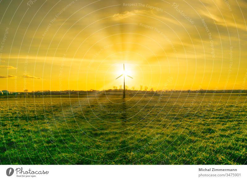Windkraftanlage mit Biogasanlage im Sonnenschein/Sonnenauf-/untergang mit grünem Weidegras Sonnenaufgang Sonnenstrahlen Sonnenuntergang Sonnenlicht