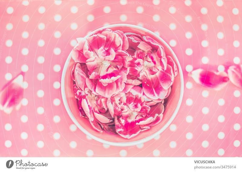 Wasserschale und schwimmende rosa Blumen auf Polka-Dot-Hintergrund, Draufsicht Schalen & Schüsseln fliegend Polkatänzer Punkt oben Aroma Aromatherapie schön