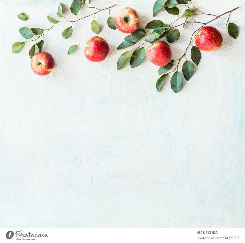 Schmackhafte reife rote Äpfel mit Zweigen und grünen Blättern auf rustikalem weißen Hintergrund, Draufsicht. Rand oder Rahmen mit Kopierraum für Ihr Design