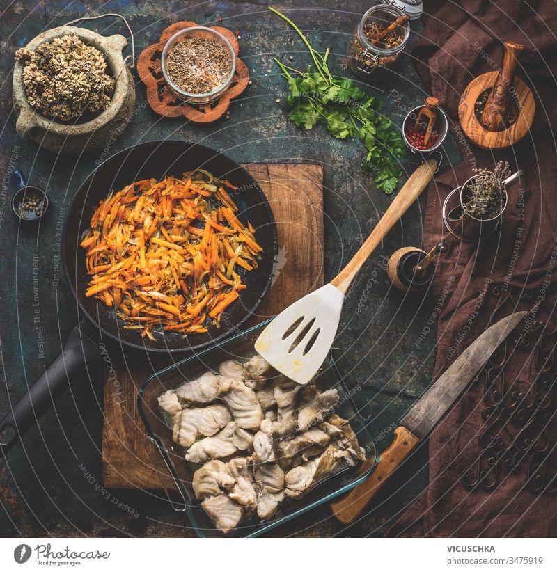 Zubereitung eines Kohlefischgerichts und Gemüsesauce auf dunklem Küchentischhintergrund mit Zutaten, Draufsicht. Konzept für gesunde Hausmannskost. Hausgemachte Küche