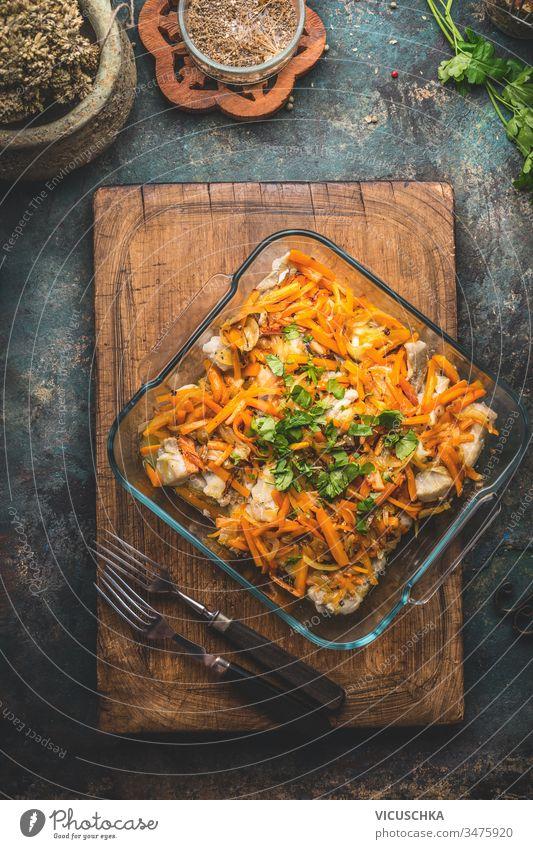 Leckeres Fischgericht mit Gemüsesauce auf Küchentischhintergrund mit Gabeln. Ansicht von oben.  Konzept der gesunden Hausmannskost. Hausgemachte Küche
