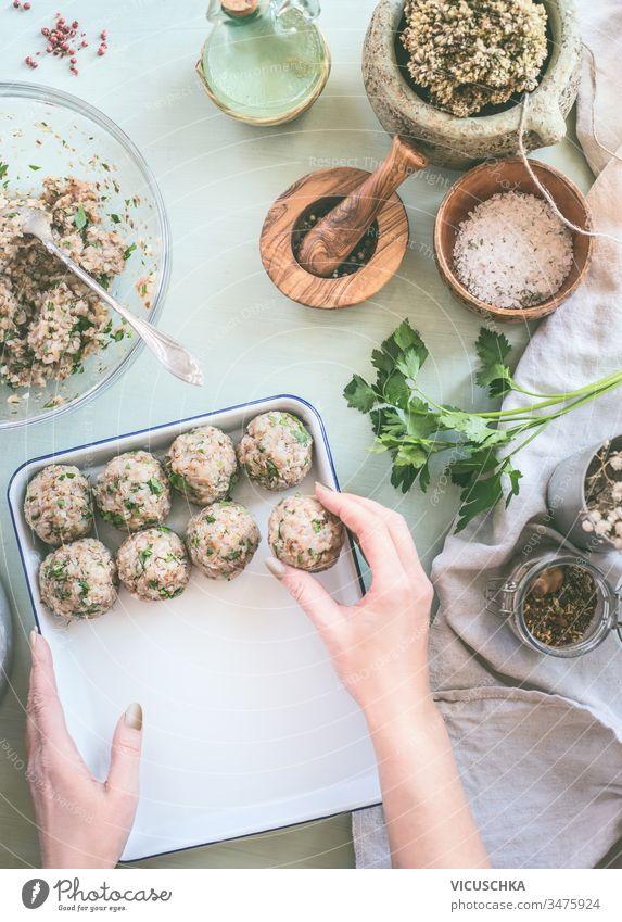 Weibliche Hand macht Buchweizenkugeln auf Küchentischhintergrund mit Kräutern und Gewürzen, Draufsicht. Gesundes hausgemachtes Essen Frau machen Bälle Tisch
