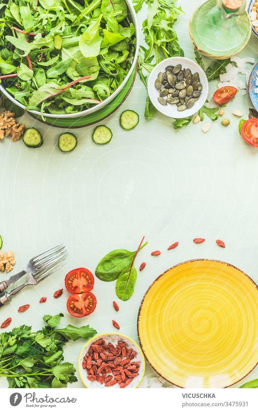 Lebensmittelhintergrund mit Salattellern. Frische grüne Salatzutaten. Salatgarnitur: Samen, Nüsse und Beeren. Gesundes Essen. Hintergrund frisch Salatbeilage