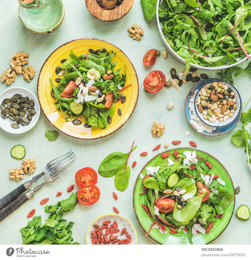 Teller mit grünem Salat auf Küchentischhintergrund mit Gabeln und Zutaten: Nüsse, Samen, junge Blätter, Olivenöldressing. Ansicht von oben. Diät. Sommerliche Küche. Gesunde Hausmannskost