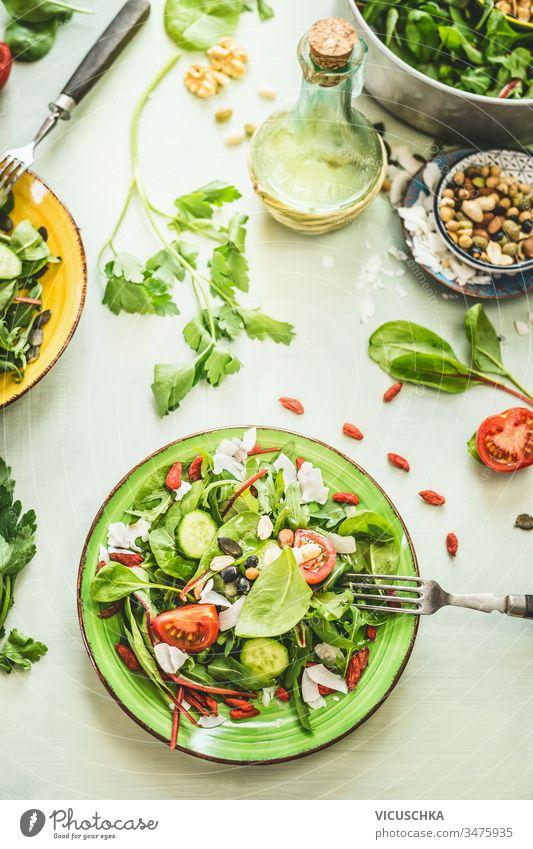Gesunder frischer grüner Salatteller mit verschiedenen Samen und Beeren auf hellem Tischhintergrund mit Olivenöl und Zutaten. Ansicht von oben Gesundheit