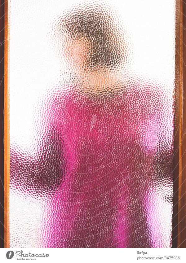 Junge Frau hinter verschlossener Tür durch Glas gesehen Mädchen zu Hause bleiben Fenster Silhouette rosa Pullover Winter gemütlich zugeklappt heimwärts