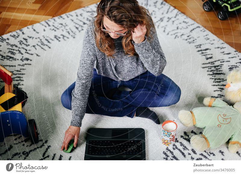 Frau sitzt im Schneidersitz im Kinderzimmer mit Spielzeug und arbeitet am Laptop Homeoffice sitzen arbeiten stayhome Teppich Computer Arbeit Erwachsener Büro