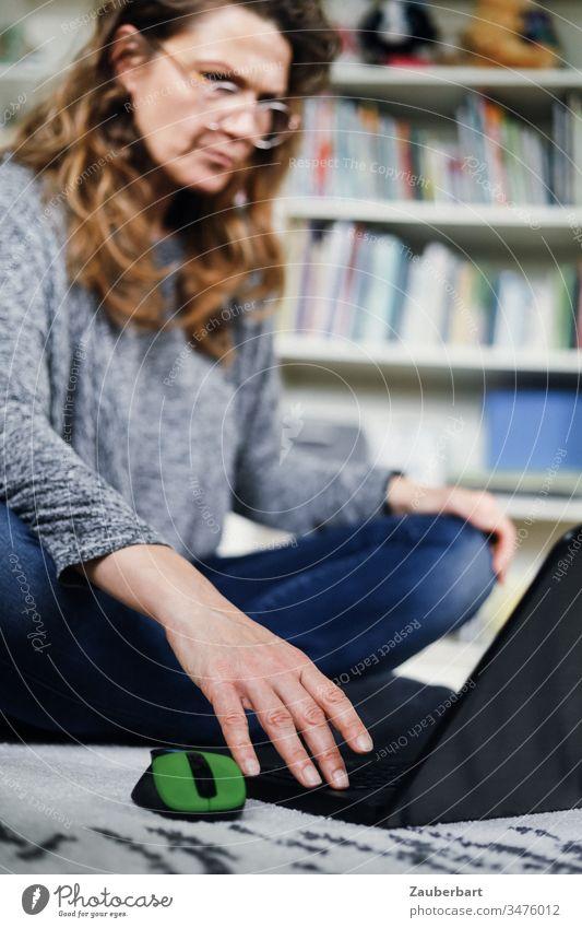 Frau sitzt im Homeoffice auf dem Boden und schaut konzentriert auf ihr Laptop genervt lesen Teppich Computer Notebook Maus Büro Business