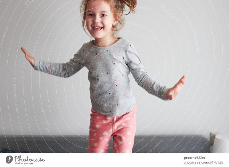 Kleines fröhliches, verspieltes Mädchen, das Spaß daran hat, morgens zu Hause im Schlafzimmer auf das Bett zu springen springend lustig Spielen Herstellung
