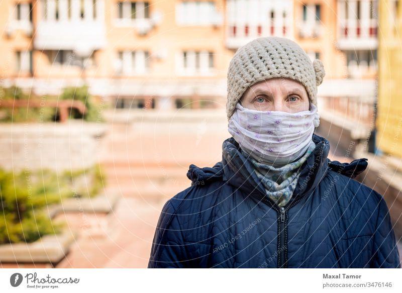 Eine arme ältere Frau trägt eine selbstgemachte Maske, um sich vor Viren zu schützen Erwachsener luftgestützt Atmung Gebäude Großstadt Ansteckung ansteckend