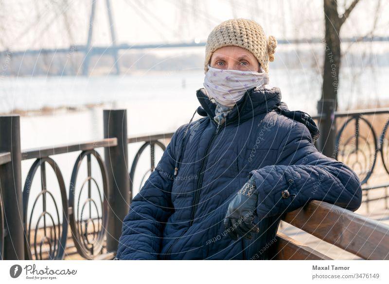 Eine arme ältere Frau trägt eine selbstgemachte Maske, um sich vor Viren zu schützen Erwachsener Bank Atmung Mantel Ansteckung ansteckend Korona Coronavirus