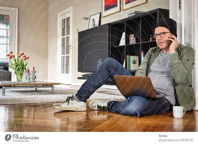 HomeOffice: der entspannte Mann sitzt wieder auf dem Boden vor seinem Notebook und freut sich auf sein Büro Wohnzimmer arbeiten von zu Hause Heimarbeitsplatz