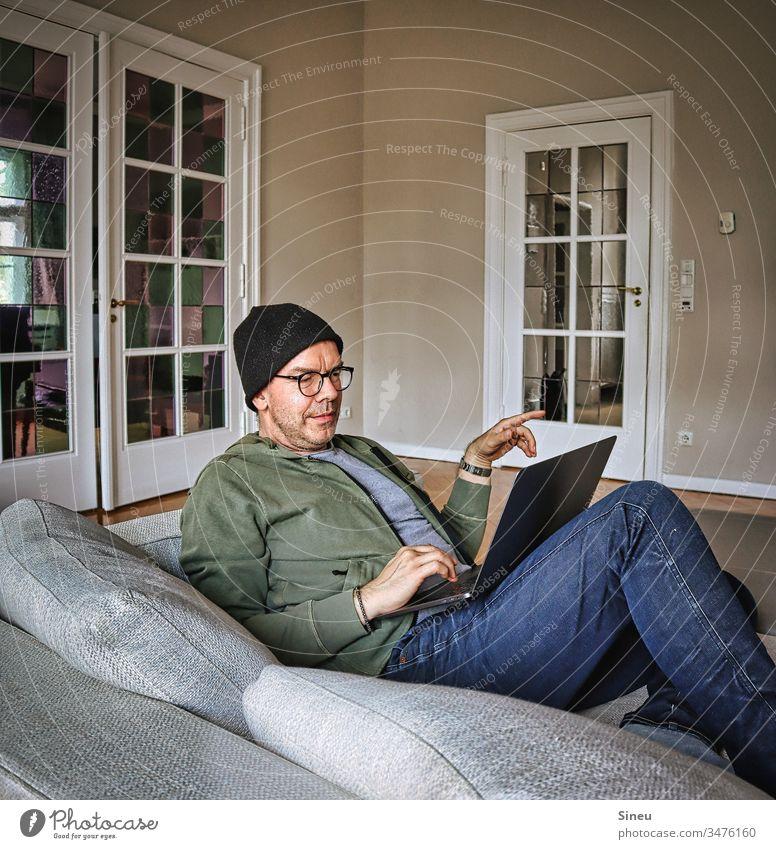 HomeOffice: immer noch entspannter Mann liegt jetzt mit seinem Notebook wieder auf dem Sofa und arbeitet Wohnzimmer Heimarbeitsplatz ein Mann alleine