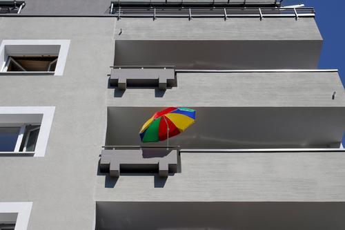 bunter sonnenschirm und graue fassade balkon balkone farbig balkonien urlaub ferien freizeit fenster haus gebäude architektur immobilie zuhause zu hause wohnen